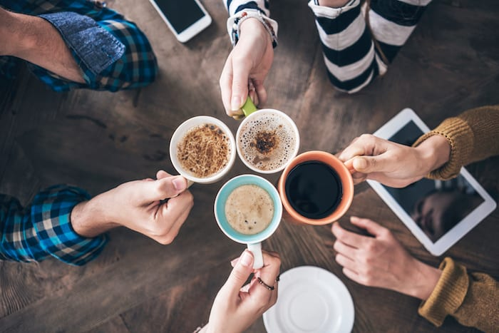 Overhead shot of four people holding cups of coffee whilst sat around a table.