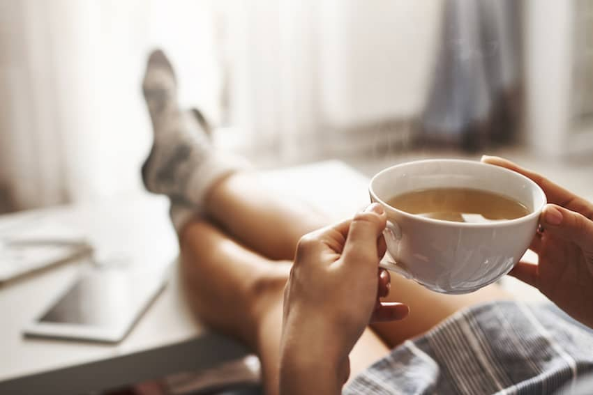 Lady sat on sofa with cup of tea in hands